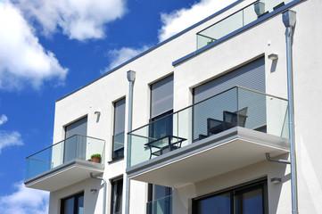 Moderne Balkone, verglast mit Metall-Geländer an Neubau-Hausfront mit Flachdach, Wasserkästen, Regenfallrohren und Edelstahl-Attika