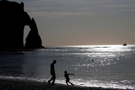 A man and a child are seen in silhouette as they play on the pebbled beach of Etretat on the Normandy coast as sunny weather arrives in France
