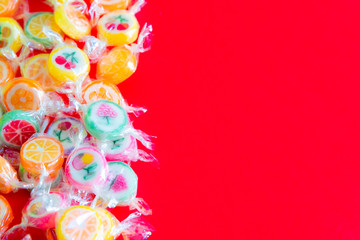 Fruit candies on red background
