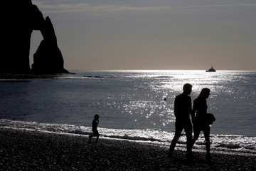 People are seen in silhouette as they walk on the pebbled beach of Etretat on the Normandy coast as sunny weather arrives in France