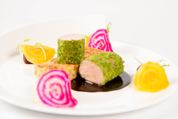 Roast pork tenderloin with crispy potato bread, marinated beetroots and green pepper sauce on a plate on a white background
