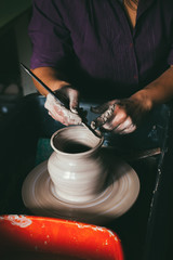 Close-up A dark-haired Woman potter in apron sculpts a deep bowl from the clay on a potter's wheel and cuts off excess clay in the workshop