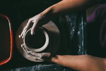 Creating a jar or vase of white clay close-up. Master crock. Man hands making clay jug macro. The sculptor in the workshop makes a jug out of earthenware closeup. Twisted potter's wheel.