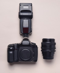 Equipment of the photographer. Digital camera, flash, lens. Top view, flat lay.
