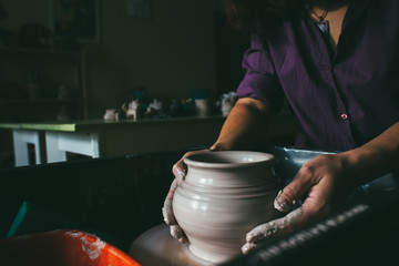 Professional female potter working with clay on potter's wheel in workshop, studio. Handmade, art and handicraft concept