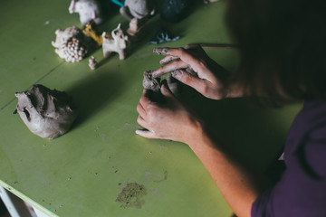 Close up of man ceramist hands holding a tool and working on sculpture details of the head on wooden table in workshop