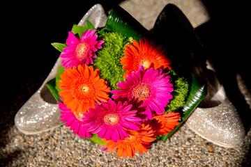 bunte Blumen für die Braut zur hochzeit. blumenstrauß dekoration mit Gerbera rosa orange Grün und Gras vor glitzernen high heels und silhouette