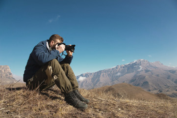 Portrait of a bearded hipster, a photographer takes pictures of his DSLR against the backdrop of snow-capped Caucasian mountains on a sunny day. The concept of a free life with tourism and photography