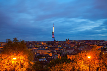 Zizkov Television Tower (circa 1992) in Prague and roof top view of dwellings around tower. Night view.