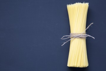 Spaghetti on dark background with copy space. Long spaghetti. Raw spaghetti. Top view. From above. Flat lay.