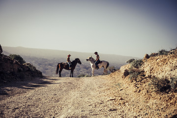emotional image with two horses and a coulpe riding in the nature