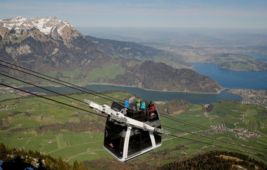 "Mount Pilatus is seen in the background as people ride the ""Cabrio"" open-air double-decker cable car system on Mount Stanserhorn mountain in Stans"
