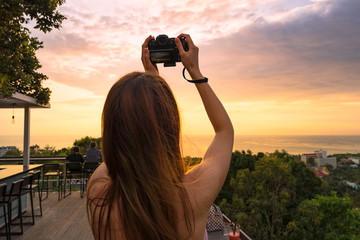 Girl with camera takes a beautiful sunset pictures over the sea from high. Back view. Average close-up
