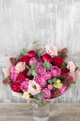 Close-up Beautiful Bouquet. Spring flowers on gray background. flower shop. Wooden table. Vertical photo
