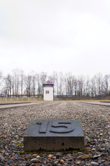 Dachau, Upper Bavaria / Germany - March 2018: A guard tower stands tall over rows of stone and rock marking the area where barracks once stood at the Dachau Concentration Camp Memorial Site.