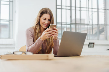 Young cheerful woman using phone at office