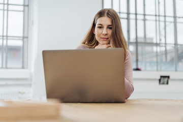 Thoughtful young businesswoman reading her laptop