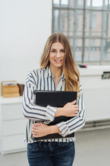 Young woman standing with binders in office