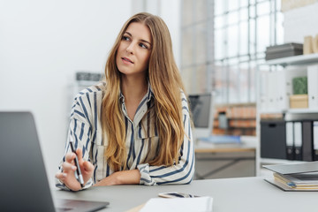 Young stylish businesswoman sitting thinking