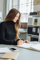 Young businesswoman sitting writing notes