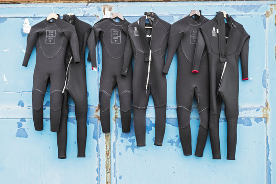 A number of wetsuits drying in summer sun on an old distressed door after use in surfing.