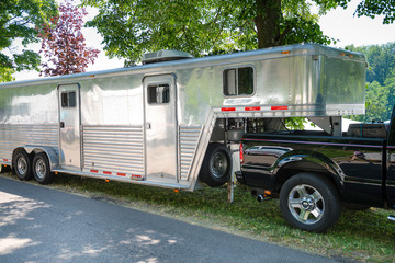 A huge silver caravan trailer with truck on a sunny summer day. Might easliy cover horses or cars in addition to the living area.