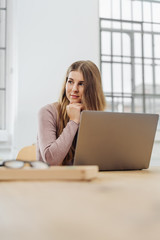 Young thoughtful woman sitting in front of laptop