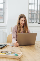 Young smiling woman working on laptop in office