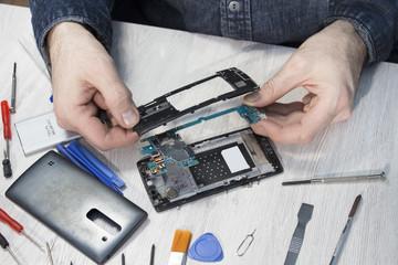 Fototapeta Naprawa telefonu komórkowego. Dłonie mężczyzny wyjmują płytkę z układem scalonym z obudowy telefonu komórkowego. obraz