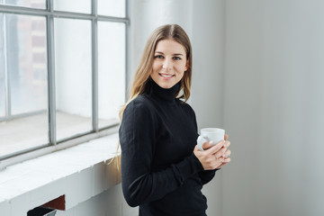 Relaxed young woman enjoying a cup of coffee