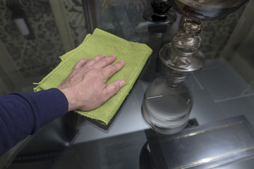 The man's hand wipes the surface of the glass table with a green rag.