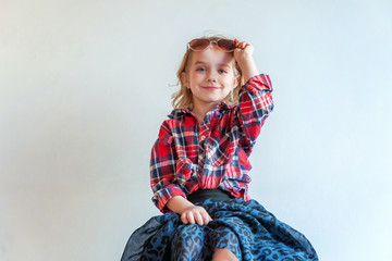 Sweet happy adorable fashion young little girl dressed like hipster hippie gipsy cowboy in sunglasses standing against white wall background in light bright room. Lifestyle people trendy concept