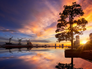 Evening sunset starburst landscape park, tree, reflection river and ship