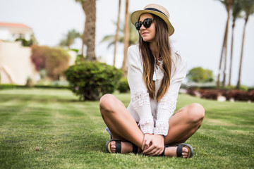 Young beauty woman in sunglasses and straw hat sitiing on grass under palm tree at beach resort