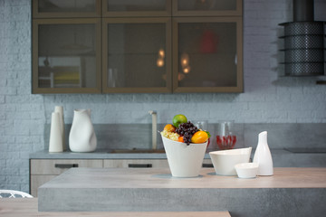 Beautiful modern kitchen interior with kitchenware and fresh fruit bowl on countertop, close-up