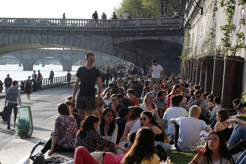 People are seen on the banks of the Seine River during sunny weather in Paris