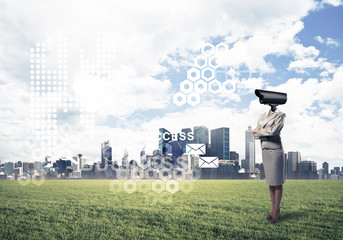Camera headed woman standing on green grass against modern citys