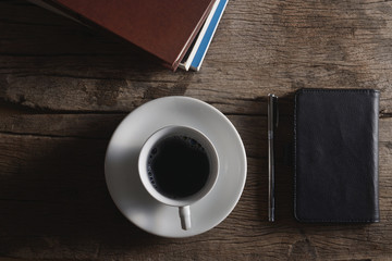 Book, pen, leather bag and coffee cup on wooden floor.