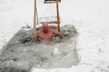Crazy elderly Russian man, swimming in the ice-hole as President Putin on Lake Seliger. Feast of the Baptism of Jesus Christ. Pyatimorsk, a baptismal ice-hole near the church of St. Innocent.