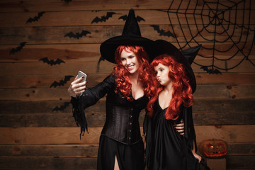 Halloween Concept - Beautiful caucasian mother and her daughter with long red hair in witch costumes taking a selfie with smartphone  ready for celebrating Halloween.