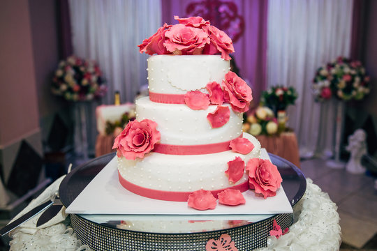 A large white cake with pink flowers