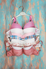 Set of different bras on wooden background