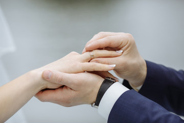 The groom puts a ring on the bride. Close up