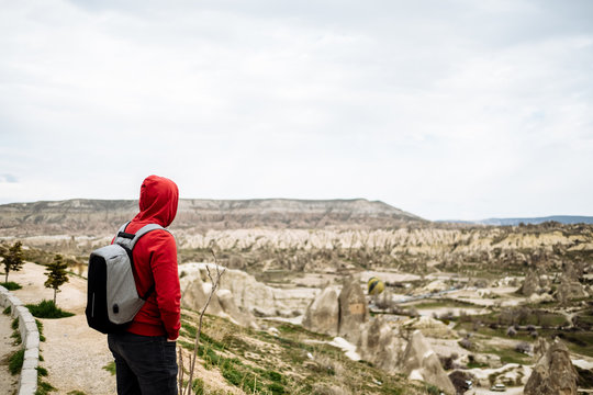 traveler in a red sweatshirt looks at the landscape of Cappadocia