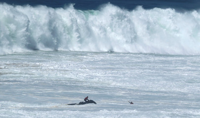 A surfer is rescued by a jet ski during a surf session at Praia do Norte in Nazare