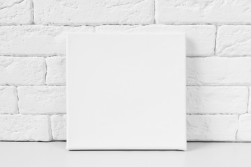 White primed canvas. Mockup poster. White brick wall on background.