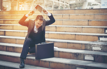 Businessman Stressed With Notebook On Stairs