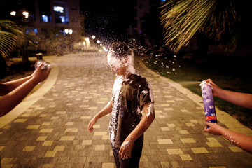 Israeli youth play with foam spray during celebrations marking Israel's 70th Independence Day in the southern city of Ashkelon
