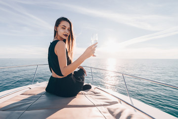 beautiful young woman in black clothes swims on her white yacht by the sea, drinks champagne