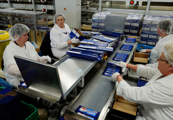 Women pack milk chocolate bars at the Lotte Wedel factory in Warsaw